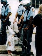 A little boy reaches for his reflection in a black cop's riot shield at a KKK rally in Gainesville, Georgia, Sep. 5 1992