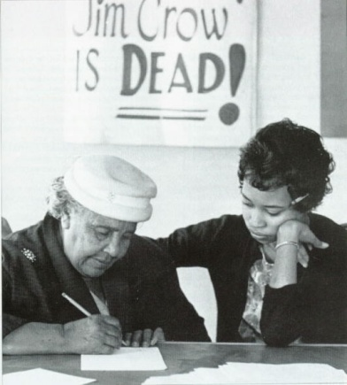 A young woman helps an older woman register to vote as part of a registration drive in the 1960's