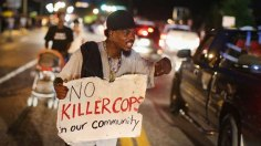 AFP_Getty_AFP-A-demonstrator-holds-a-sign-along-West-Florissant-Avenue-to-protest-the-shooting-death-of-Michael-Brown-in-Ferguson-Missouri-on-August-14-2014