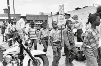 Police lead a group of children off to jail following their arrest for protesting against racial discrimination in Birmingham, Alabama.
