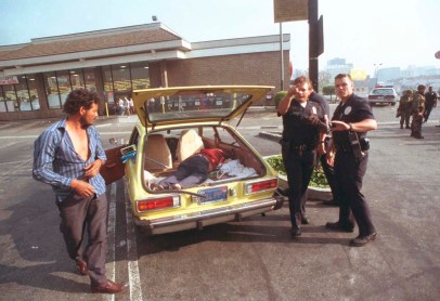 Police officers investigate a body found in a vehicle outside Ralph's supermarket during the third day of the Los Angeles Riots in Los Angeles