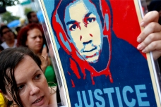 Quintera from Miami holds an image of Martin at a rally in Miami, Florida