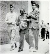 Two white young men help a badly beaten black man during the Detroit race riots. June 21, 1943